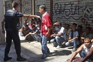 Un policía griego mantiene retenidos a unos inmigrantes residentes en Atenas. | Efe