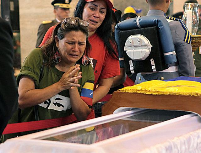 """CARACAS -- En un sorpresivo giro a las ceremonias funerarias por la muerte del presidente Hugo Chávez, el gobierno venezolano anunció el jueves que el cuerpo del mandatario será embalsamado y quedará expuesto al público de manera indefinida en una urna de cristal, en lugar de enterrarlo el viernes como se había previsto.""""Se va a preparar el cuerpo del comandante presidente, a embalsamarlo para que quede abierto eternamente… así como está Ho Chi Minh, como está (Vladimir) Lenin, como está Mao Tse-Tung"""", declaró el vicepresidente ejecutivo y presidente en funciones, Nicolás Maduro..""""Quedará el cuerpo de nuestro comandante en jefe embalsamado en el Museo de la Revolución de manera especial, para que pueda estar en una urna de cristal y nuestro pueblo pueda tenerlo por siempre"""", agregó.Unas horas antes del anuncio, la sorpresa se produjo en el Aeropuerto Internacional Simón Bolívar cuando se dio a conocer la llegada del gobernante cubano Raúl Castro, cuya asistencia a los actos fúnebres no había sido anunciada.La inesperada llegada de Castro fue transmitida en vivo por la cadena de televisión oficial venezolana VTV. El gobernante cubano fue recibido por el ministro venezolano de Relaciones Exteriores, Elías Jaua, y una pequeña guardia de honor militar, pero no hizo ninguna declaración pública.Castro fue seguido unos minutos más tarde por la presidenta de Brasil, Dilma Rousseff, y su predecesor, Luiz Inácio Lula da Silva. Maduro dijo que el presidente iraní Mahmoud Ahmadinejad llegaría la noche del jueves o la madrugada del viernes.Maduro indicó que se les pedirá a las grandes multitudes que aún esperan la oportunidad de desfilar ante el ataúd de Chávez que regresen después del funeral de Estado del viernes porque la posibilidad de visitar el catafalco se extenderá durante al menos siete días más. No estaba claro si la visita al ataúd durante esos siete días se realizará en la Academia Militar o en el Museo de la Revolución.La llegada de Castro terminó con la especulació"""