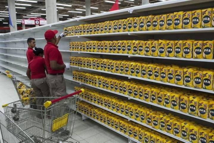 Trabajadores de un supermercado perteneciente a la red pública de alimentación del gobierno reponen los productos en una estantería, este lunes en Caracas. FOTOS: SANTI DONAIRE EFE Read more here: http://www.elnuevoherald.com/noticias/mundo/america-latina/venezuela-es/article6141300.html#storylink=cpy